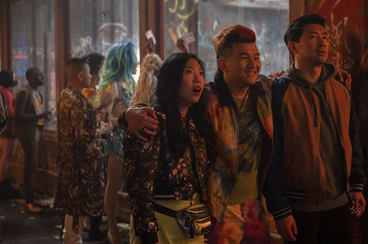 Awkwafina as Katy, and Simu Liu as Shang, stare in open mouthed shock at something out of frame as Ronny Chieng as Jon Jon embraces them both while looking amused.