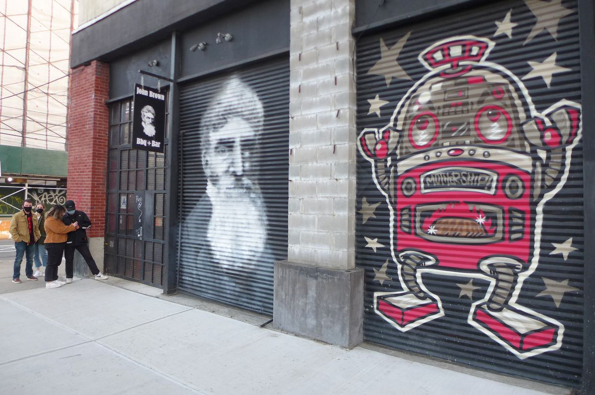 The outside of a warehouse spaces with murals of a space ship and John Brown.