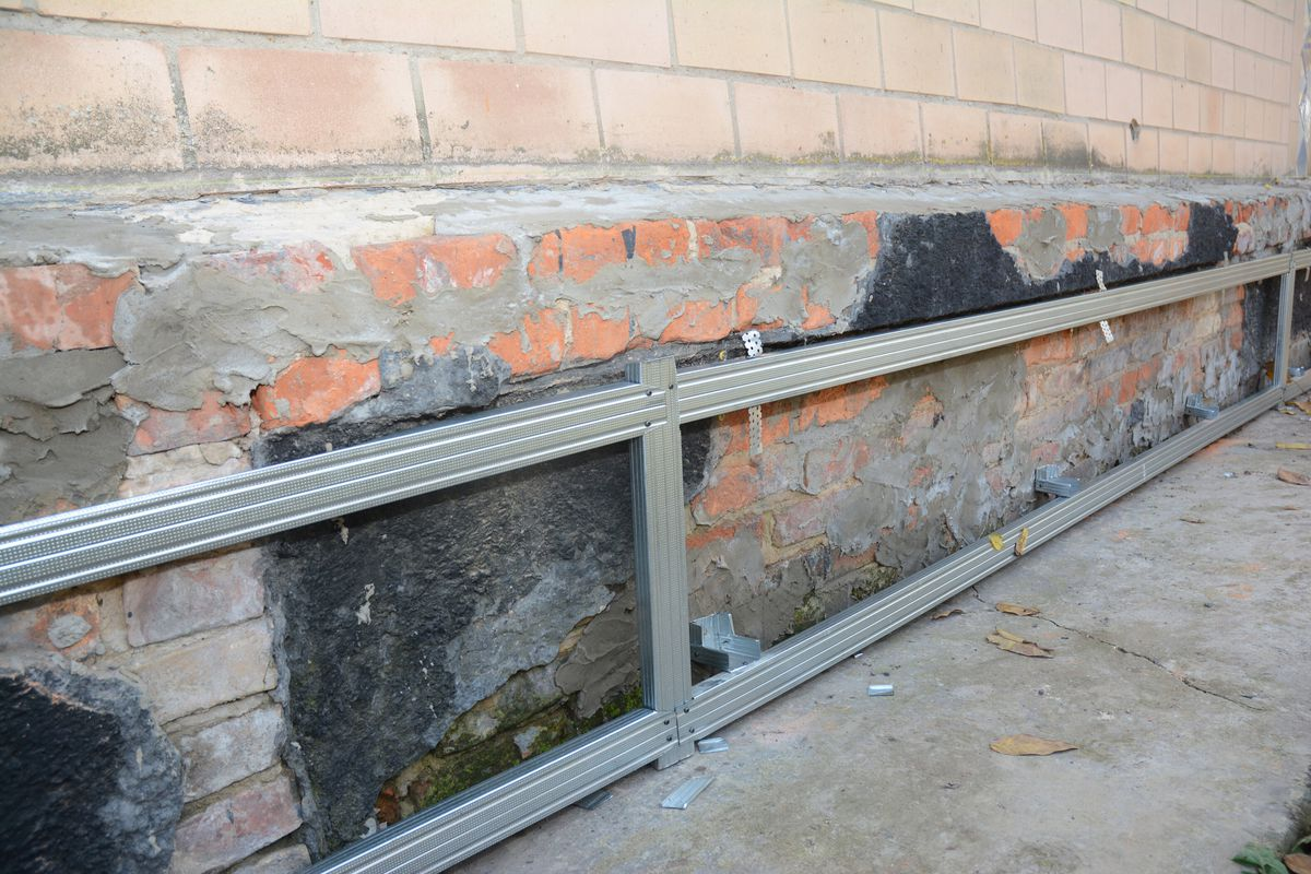 A brick home undergoing foundation repair with steel rods.