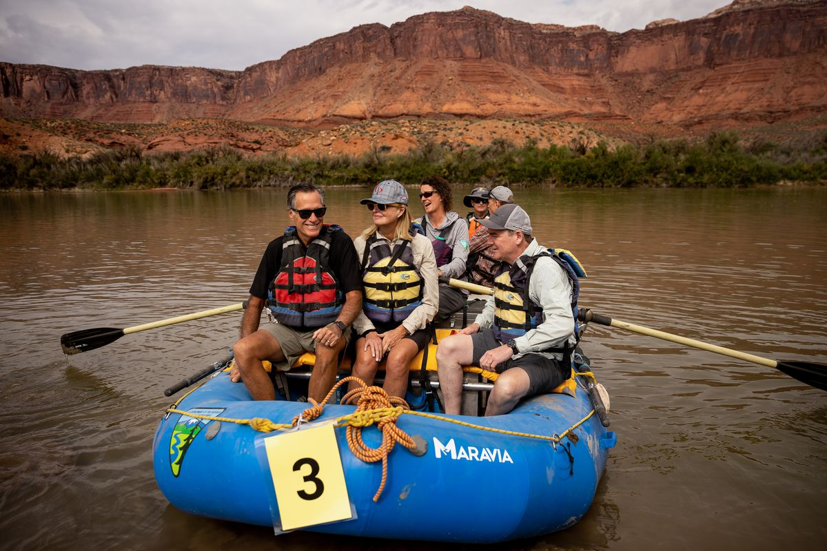 Sen. Mitt Romney, his wife, Ann, and Sen. Michael Bennet, D-Colo., sit together in a raft while they float a section of the Colorado River northeast of Moab.