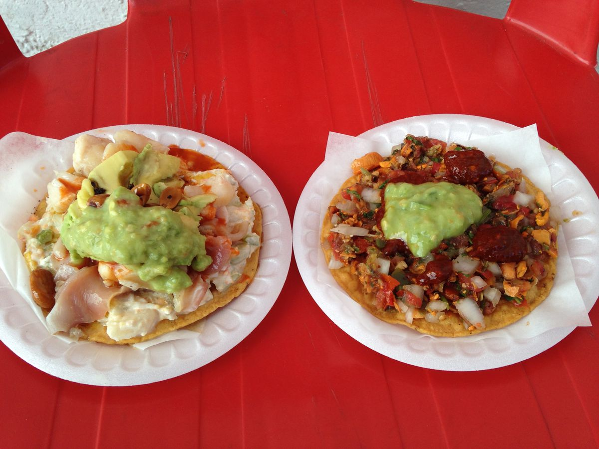 Two plates with tostadas topped with fresh seafood, vegetables, guacamole, and salsas on a bright wooden table