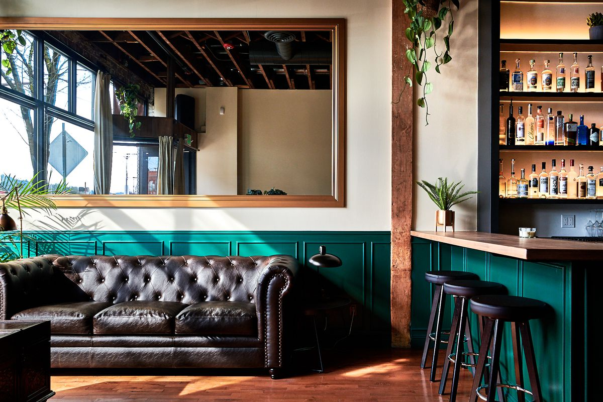 A black couch sits under a large mirror at Lulu, with teal backsplash below white walls