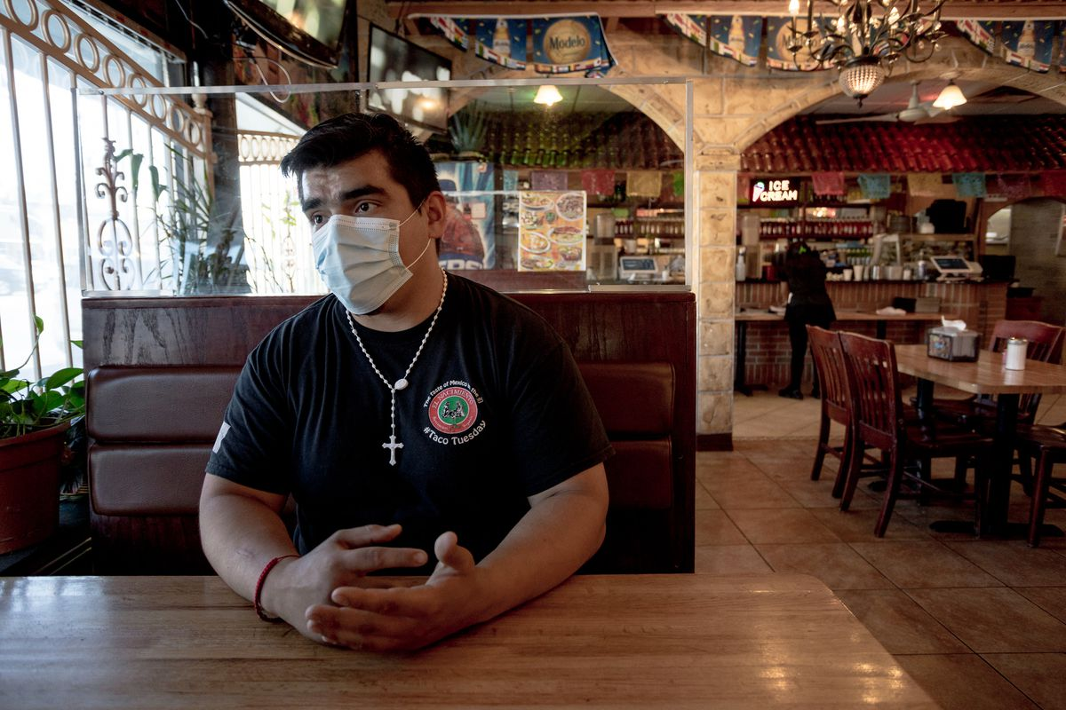 Jose Padilla sits at a booth surrounded by plexiglass wearing a blue paper surgical mask.