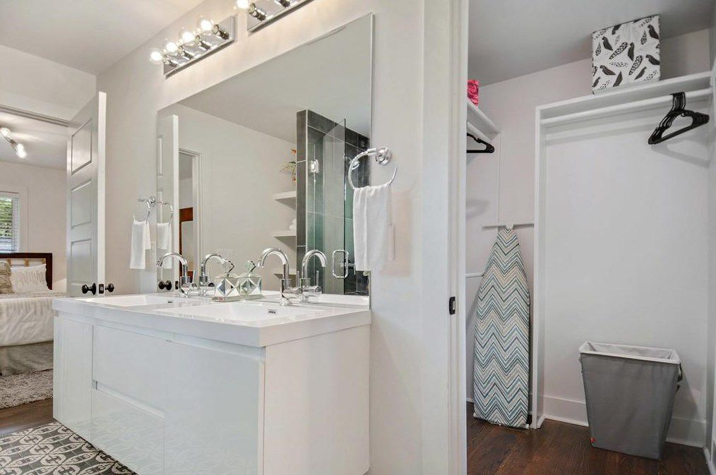 A white master bathroom with a walk-in closet.