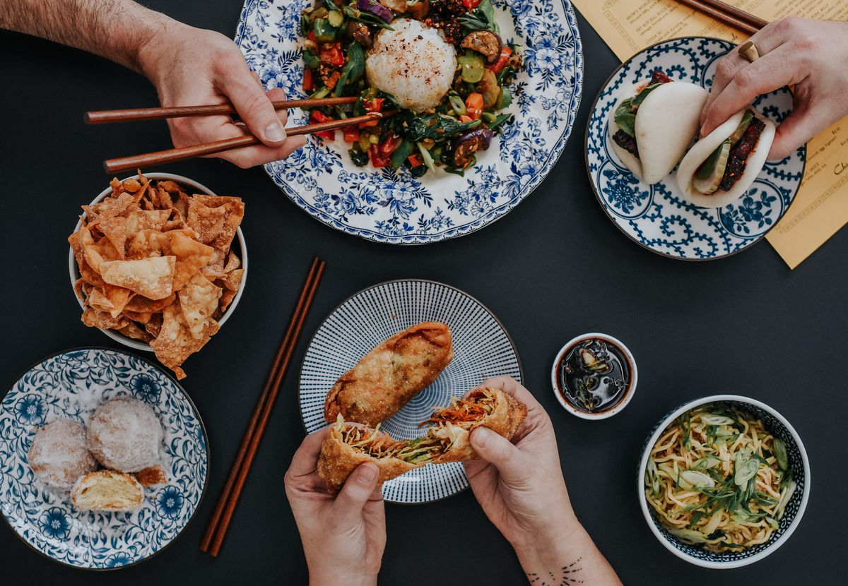 A family-style feast with people grabbing boas, using chopsticks to pick up stir-fry and tearing into egg rolls from Mow's Chinese Kitchen in Alpharetta, GA