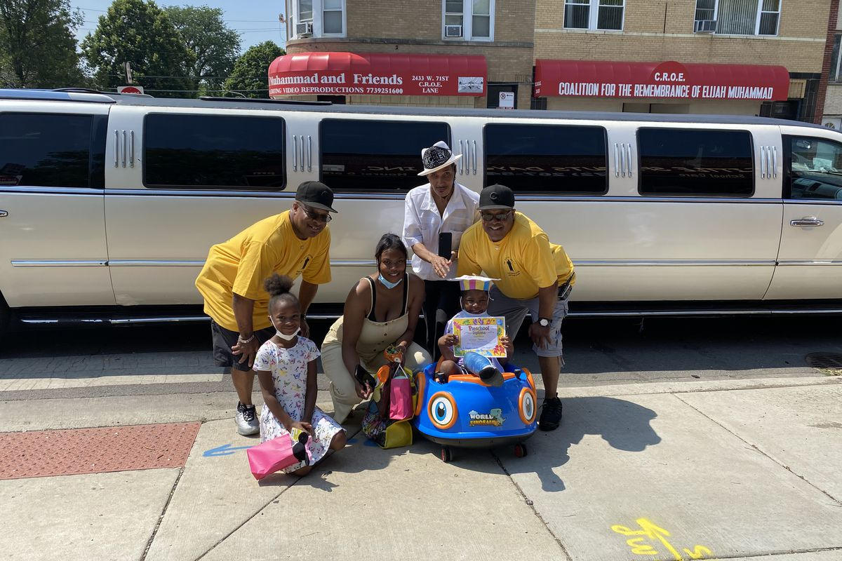 Wisdom Parker, 5, and his family pose with 100 Men Standing and Robert Money in front of the limousine they were surprised with Friday morning.