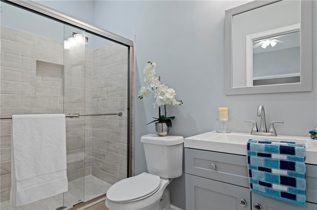 Bathroom with glassed-in shower, toilet, and vanity with towel on it.