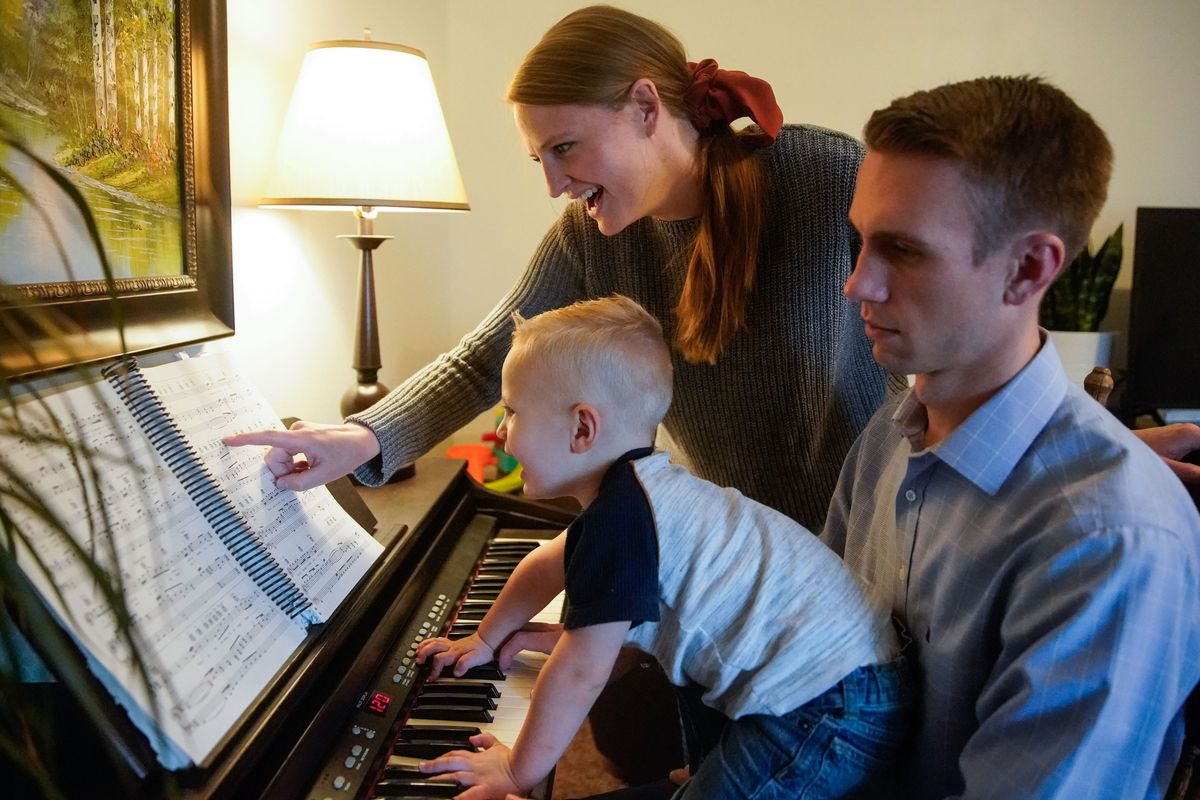 Elissa George points out a music note to her son Tanner, 2, as her husband Austen George plays the piano at their house in Provo on Friday, Oct. 8, 2021.