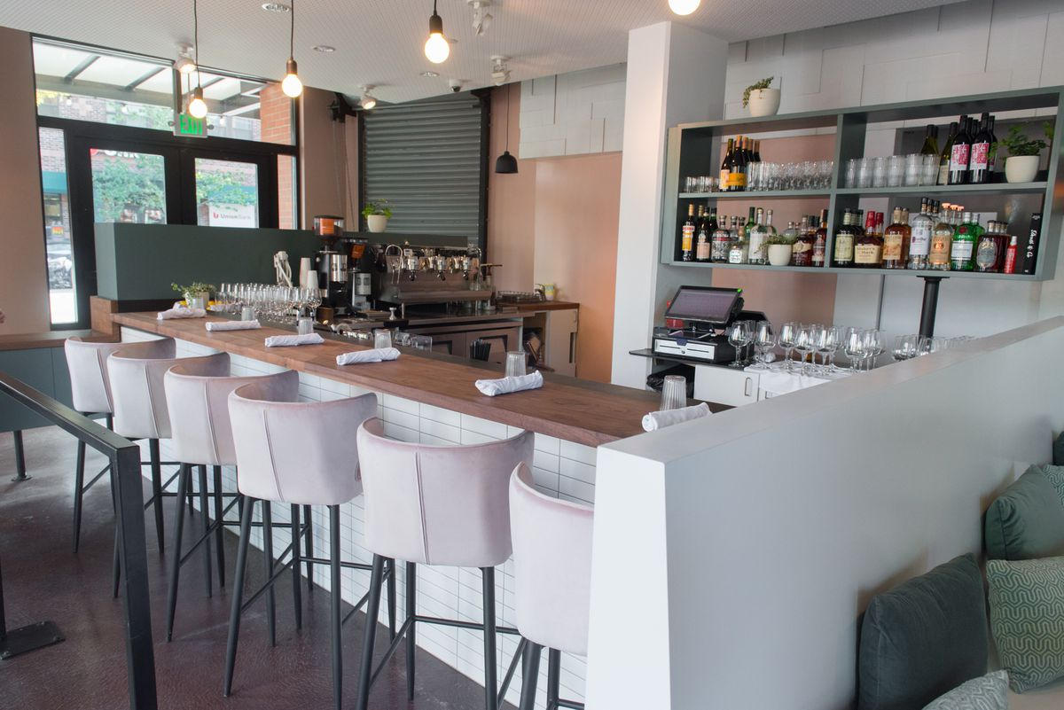 A closeup of the Eden Hill Provisions bar with pink stools and shelves of liquor bottles.