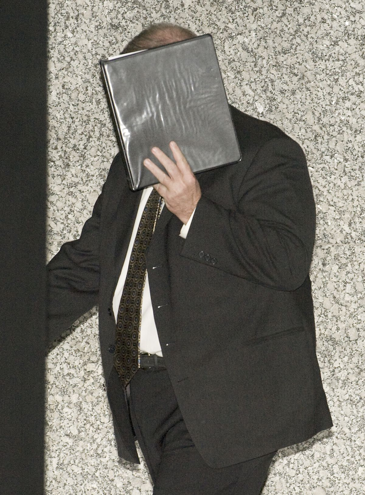 Glenn Lewellen covers his face as he leaves the Dirksen Federal Building in 2011.