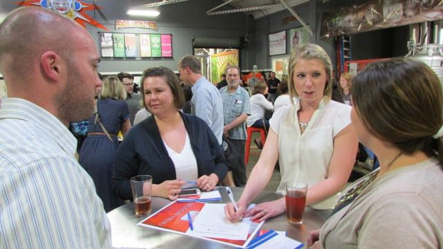 """A team that called itself """"United By Beer"""" crafts an answer during Education Trivia Night at Sun King Brewery sponsored by Chalkbeat and WFYI Public Media. Team members include representatives from United Way and former IPS principal Sheila Dollaske."""