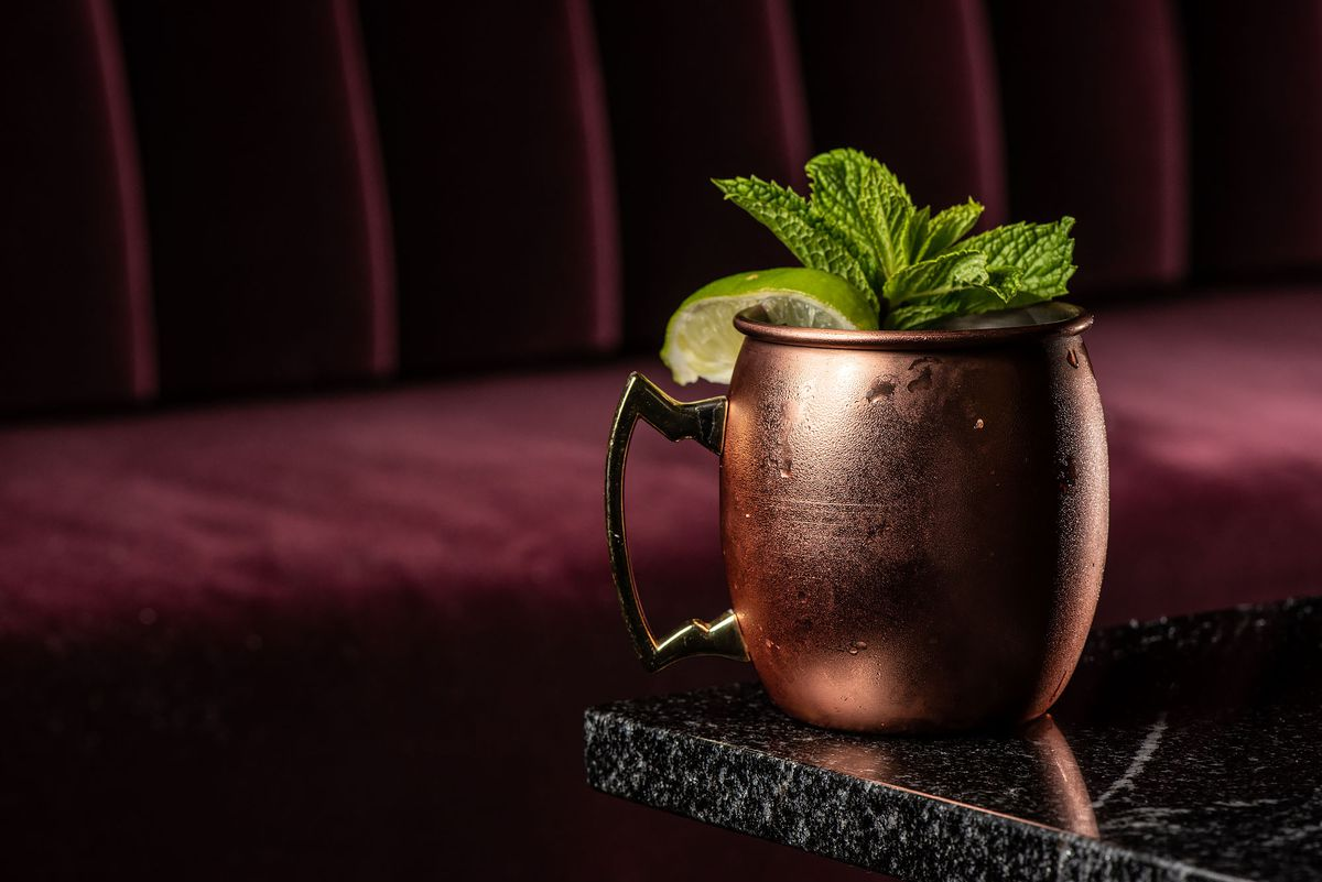 A Moscow mule in front of a velvet seat.