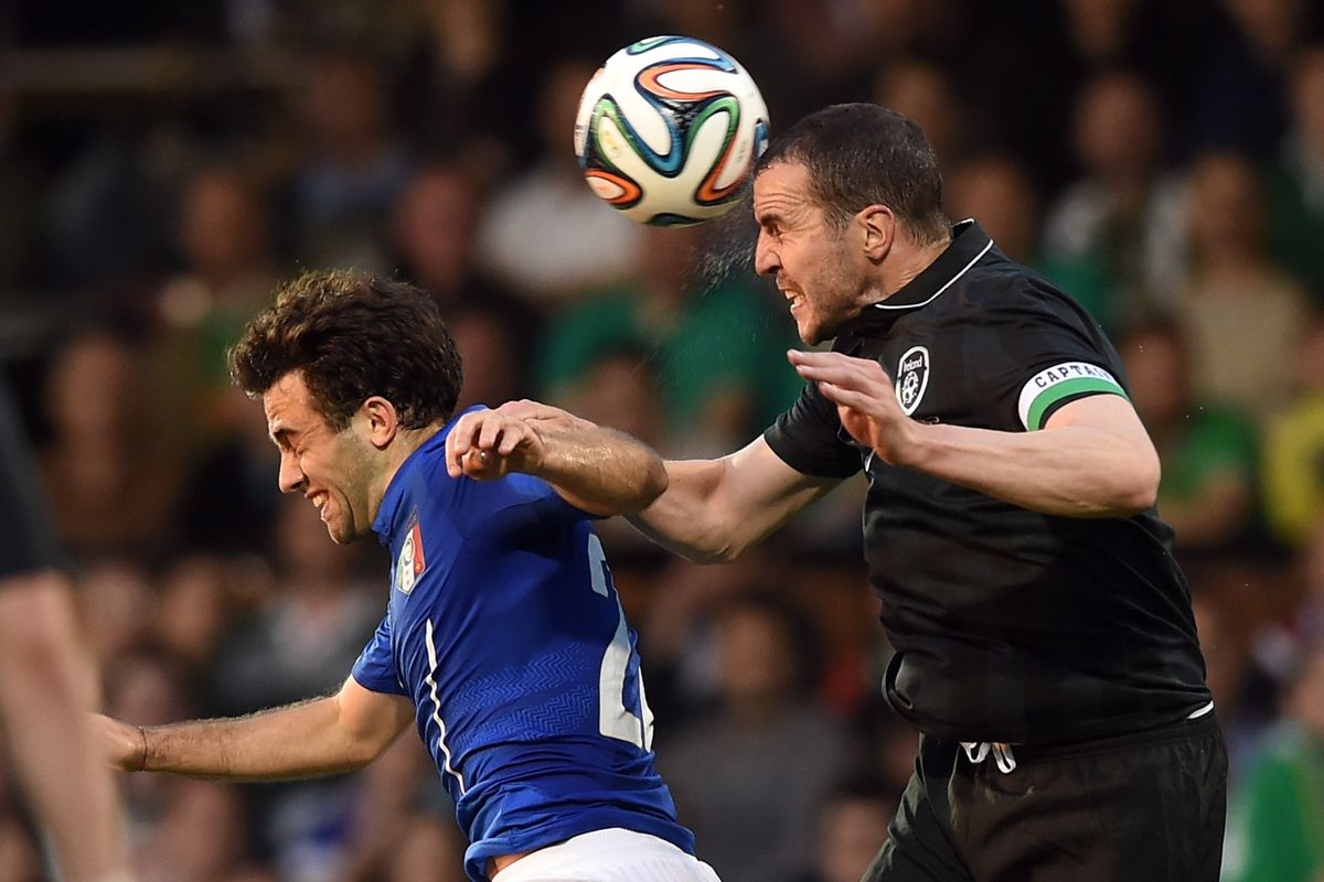 O'Shea heading the ball away from danger against Italy