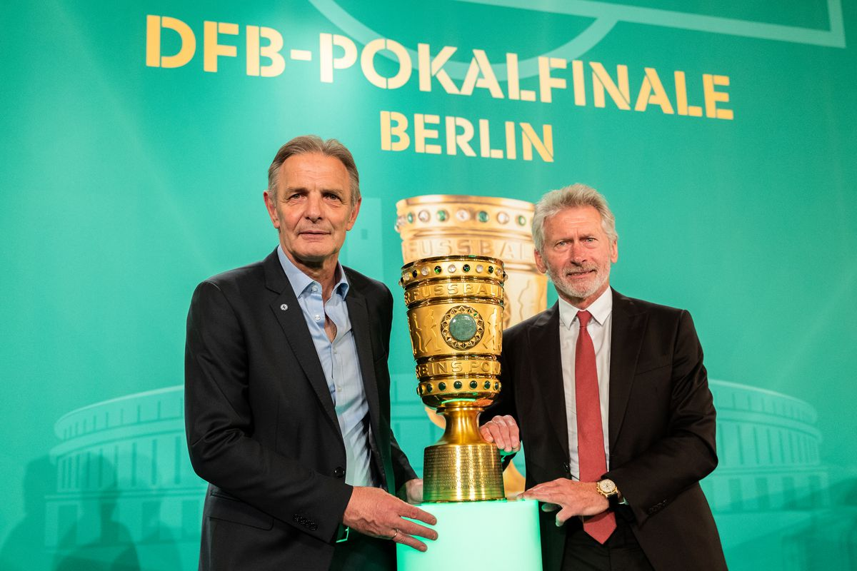 BERLIN, GERMANY - APRIL 27: Former football players Karl-Heinz Koerbel and Paul Breitner pose with the cup during the DFB Cup Handover at Wappensaal of the Rote Rathaus on April 27, 2018 in Berlin, Germany.