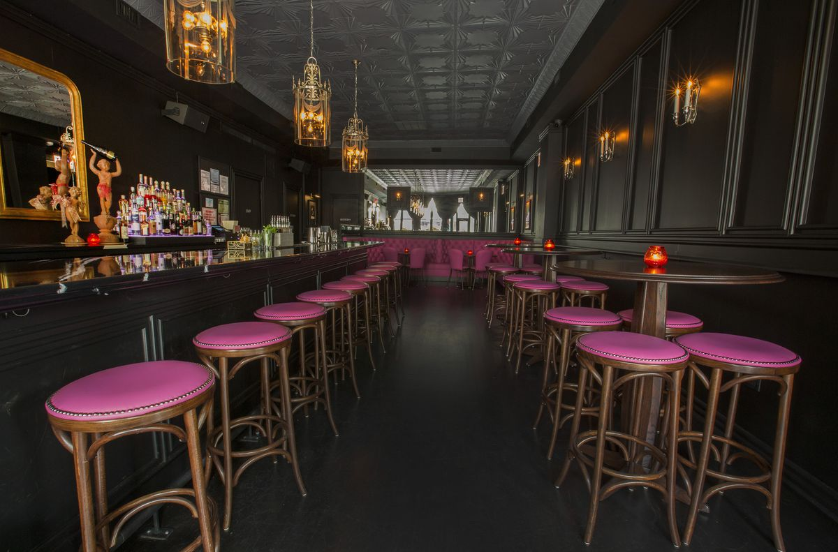 A view of a bar, straight to the back with pink bar stools, vintage gold light fixtures and liquor stacked on the left.