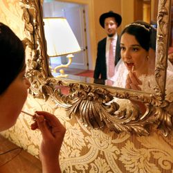 Chaya Zippel puts lip gloss on before entering her wedding reception t the Grand America Hotel in Salt Lake City on Monday, Sept. 12, 2016. She married Rabbi Mendy Cohen.