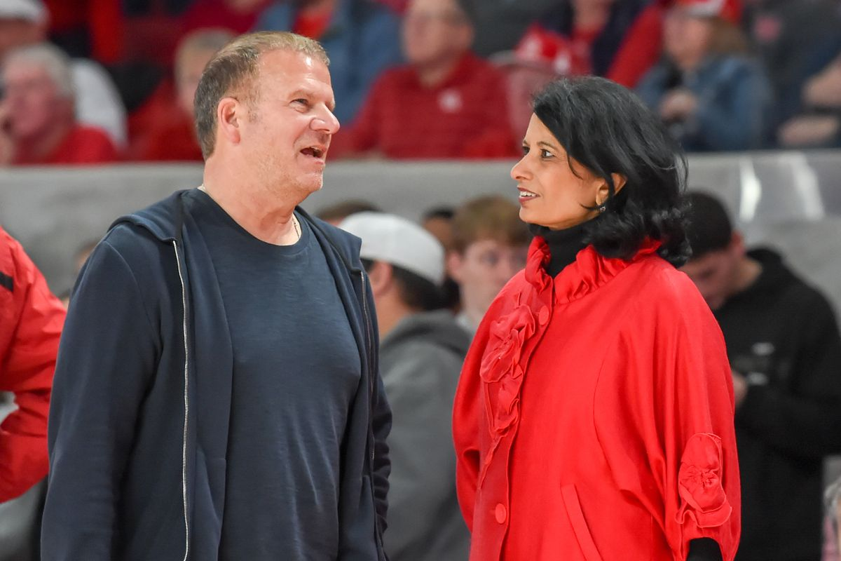 Tilman Fertitta shares a moment to visit with UH Chancellor Renu Khator during a timeout during the basketball game between the Temple Owls and Houston Cougars on January 31, 2019 at Fertitta Center in Houston, Texas.