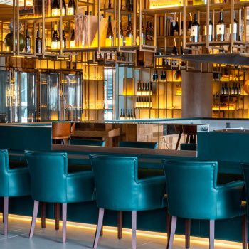 A bar with velvet blue stools and gold backlighting highlighting an architectural display of wine bottles