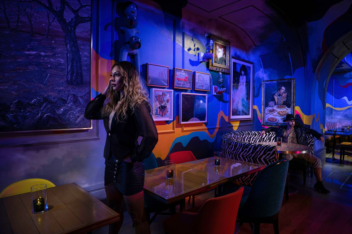 A dining room with bluish purple lights and two people standing in it with art on the walls.