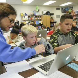 Teacher Lisa Hubbard helps Carson Groves and Stefan Sandoval at East Midvale Elementary on Monday, Sept. 25, 2017.