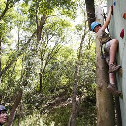 Logan Flanagan, 11, right, looks down at his instructor while climbing a rock wall during activity time at Camp Tracy in Mill Creek Canyon on Friday, July 22, 2016.
