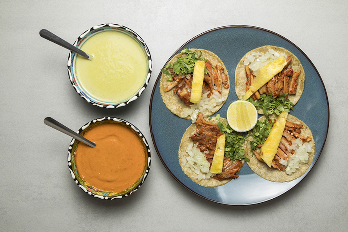 Four tacos al pastor with two salsas, one light green and one deep orange, at La Chingada, one of London's best new restaurants