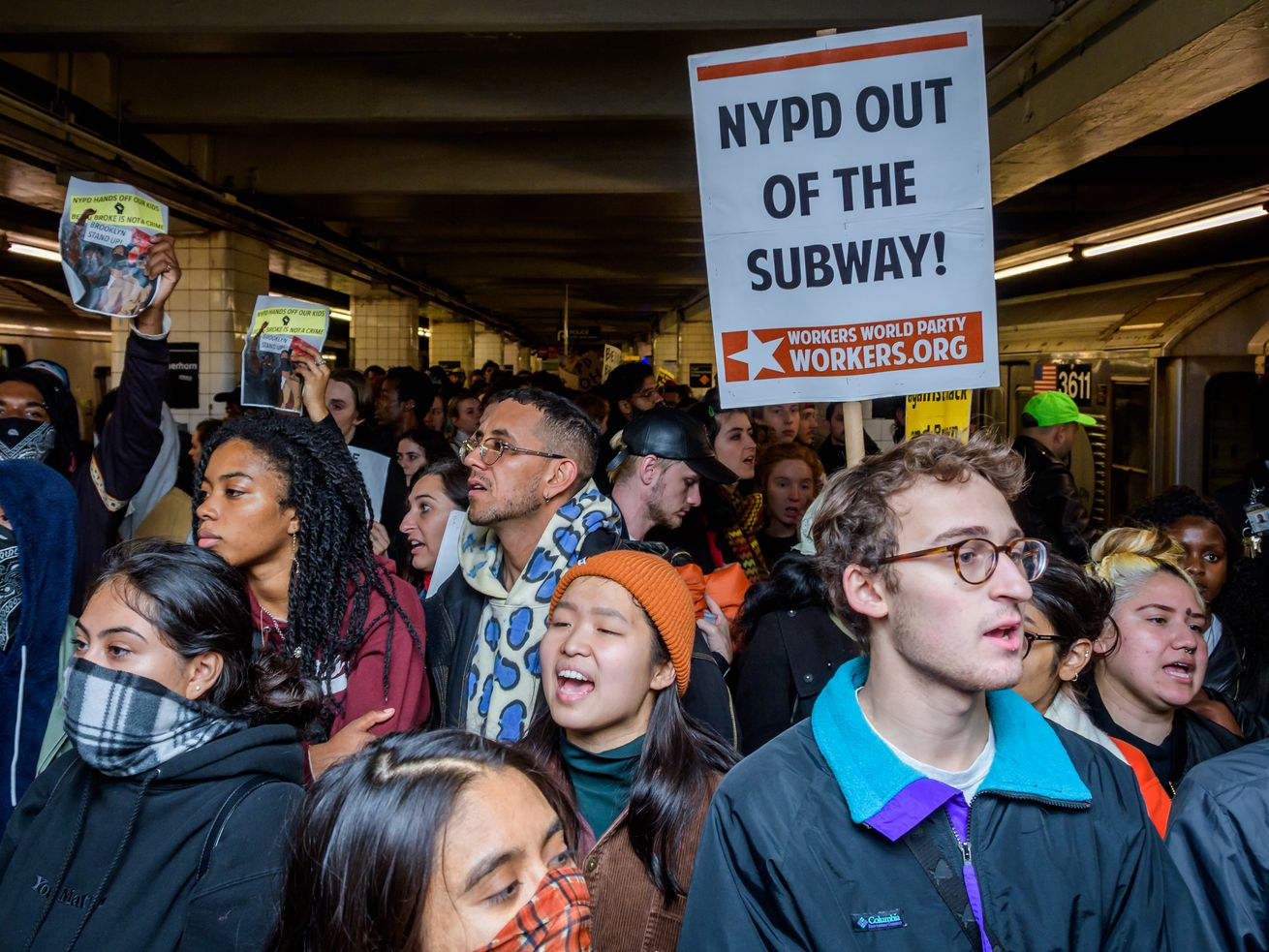 "Hundreds of protesters took over a subway platform in Brooklyn. One holds a sign that reads, ""NYPD out of the subway!"""