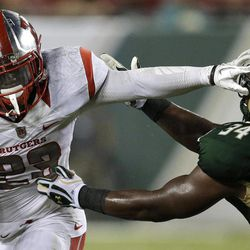 Rutgers running back Jawan Jamison (23) stiff-arms South Florida linebacker Devekeyan Lattimore (34) during the second quarter of an NCAA college football game Thursday, Sept. 13, 2012, in Tampa, Fla.