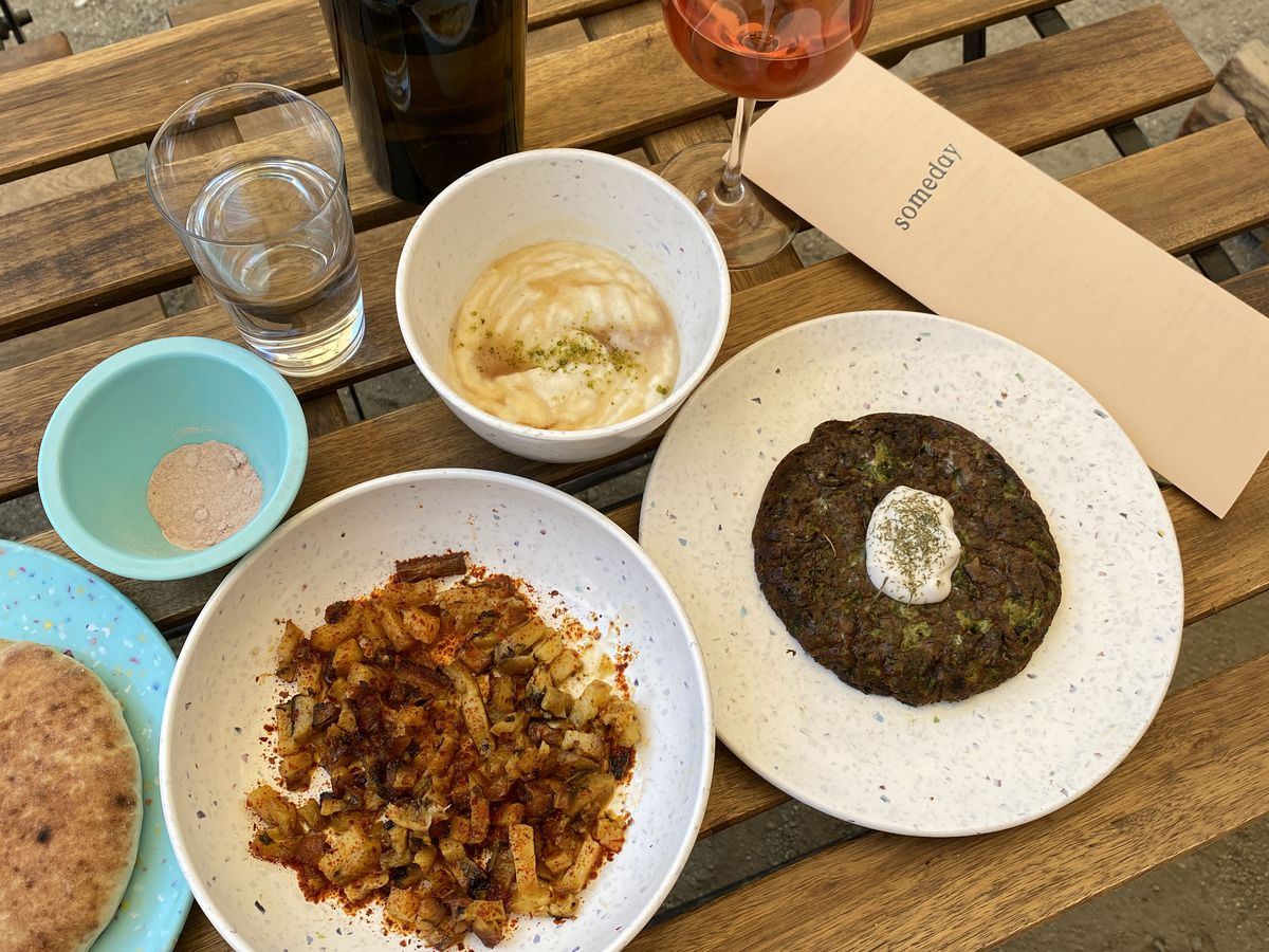 A photo of several brunch dishes at Alley Mezza, including vegan clotted cream with honey, herbed omelette, and roasted potatoes, accompanied by a glass of rose from Someday