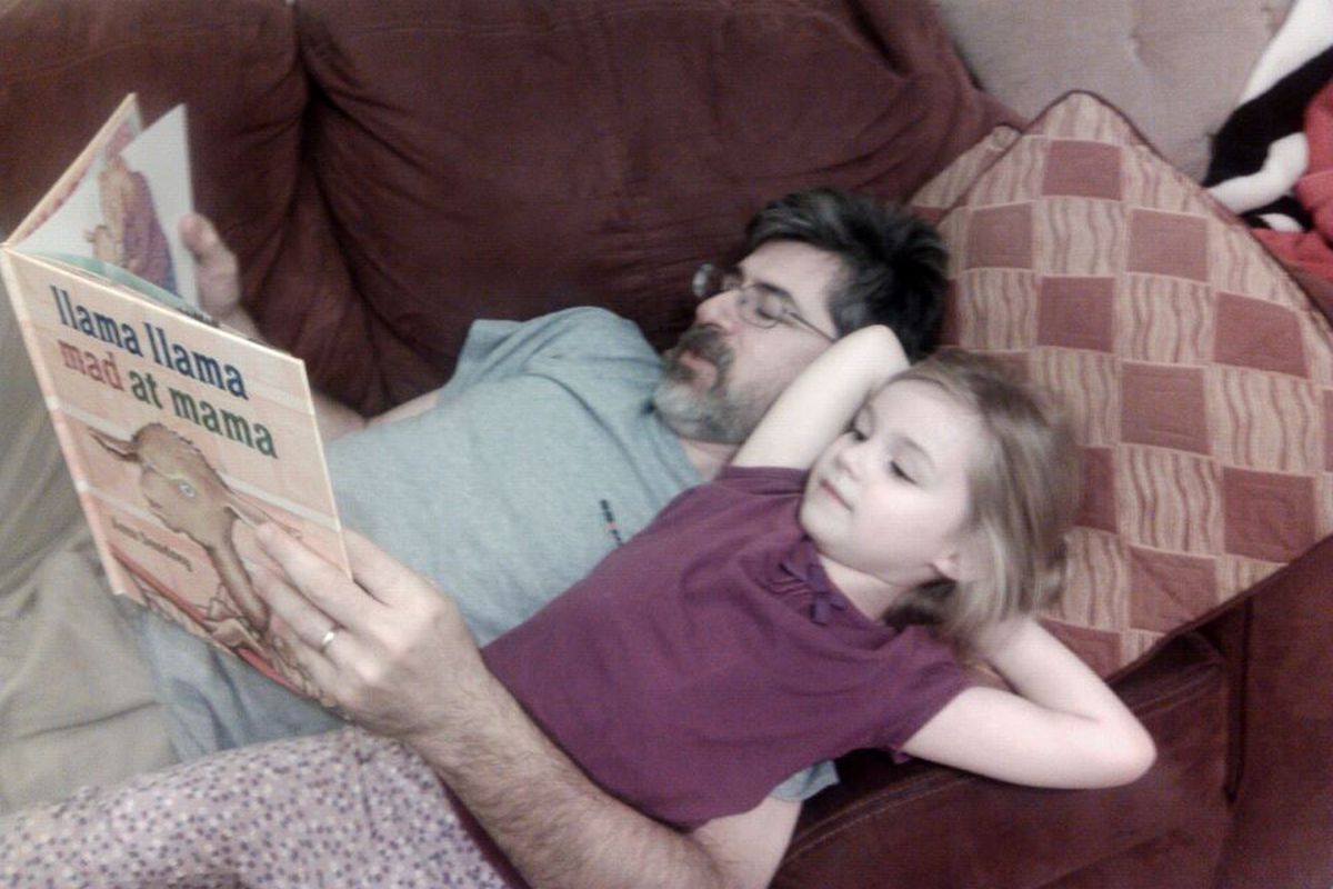 I couldn't get the photo editor to cooperate, and this is supposed to be posted instantaneously, so here's a picture of me reading to my daughter. (Photo credit: My wife.)