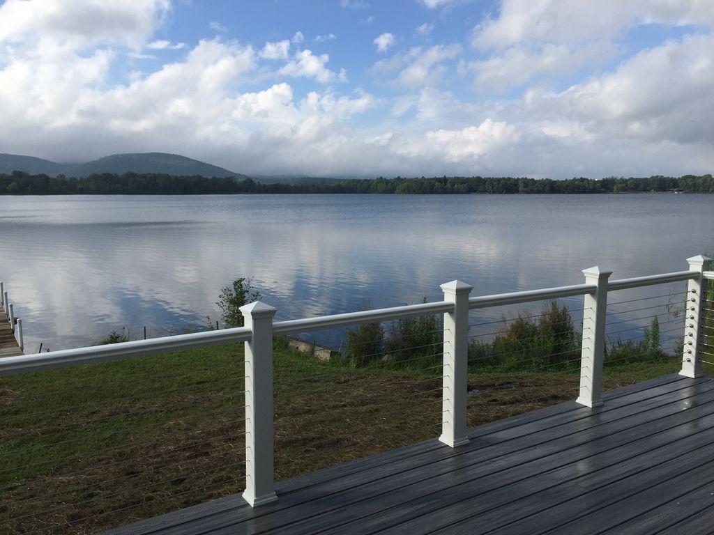A deck in front of a lawn in front of a lake.