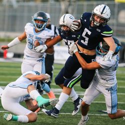 Ridgeline's Evan Webb (5) is brought down by Sky View's Carson Dunkley (22) during a high school football game at Ridgeline High School in Millville on Thursday, Sept. 17, 2020.