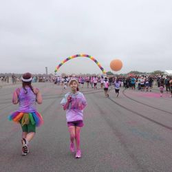 Daphne Brass (right) tells her mom to stop taking pictures and start running toward the finish at the The Color Run 5K.