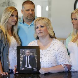 FILE - Laurie Holt holds a photograph of her son Josh Holt, while daughters Jenna, left, Katie, right, and husband Jason look on at her home Wednesday, July 13, 2016, in Riverton, Utah. Josh Holt, an 24-year-old American man jailed in Venezuela has been allowed to meet with U.S. diplomats two weeks after he and his new bride were arrested on weapons charges, a United States official said Wednesday, July 13, 2016.
