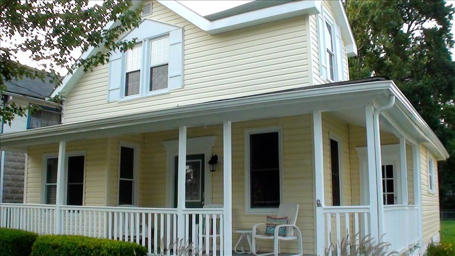 A yellow cottage in North Beach, Maryland, with a porch.