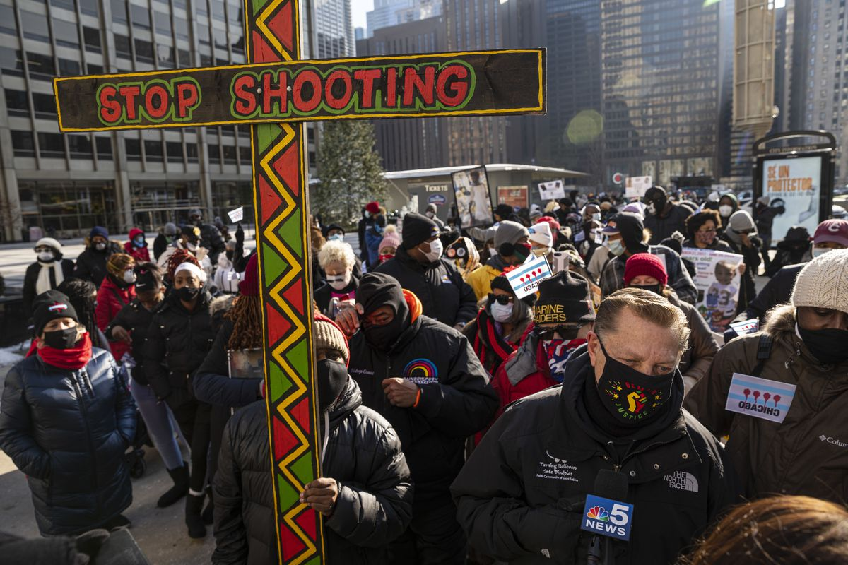 A protestor holds up a large wooden cross during a protest against the violence in the city of Chicago on N. Michigan Ave in Magnificent Mile, Thursday, Dec. 31, 2020.
