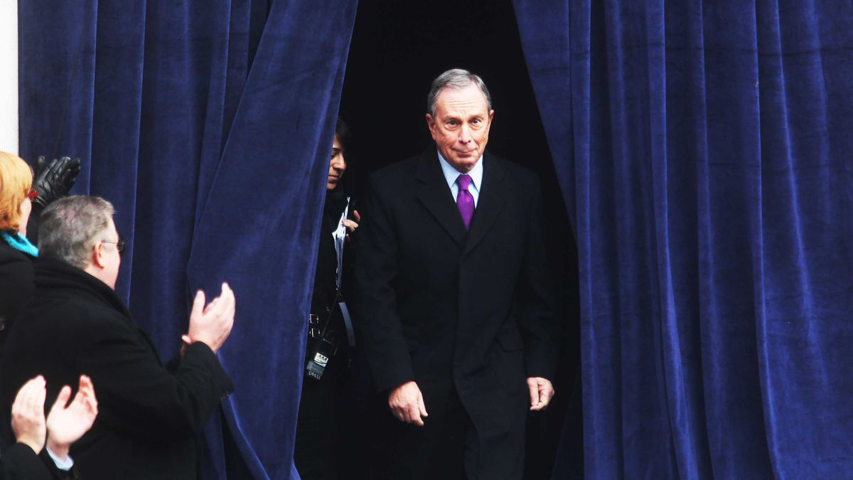 Mike Bloomberg steps through a curtain while the people around him applaud.