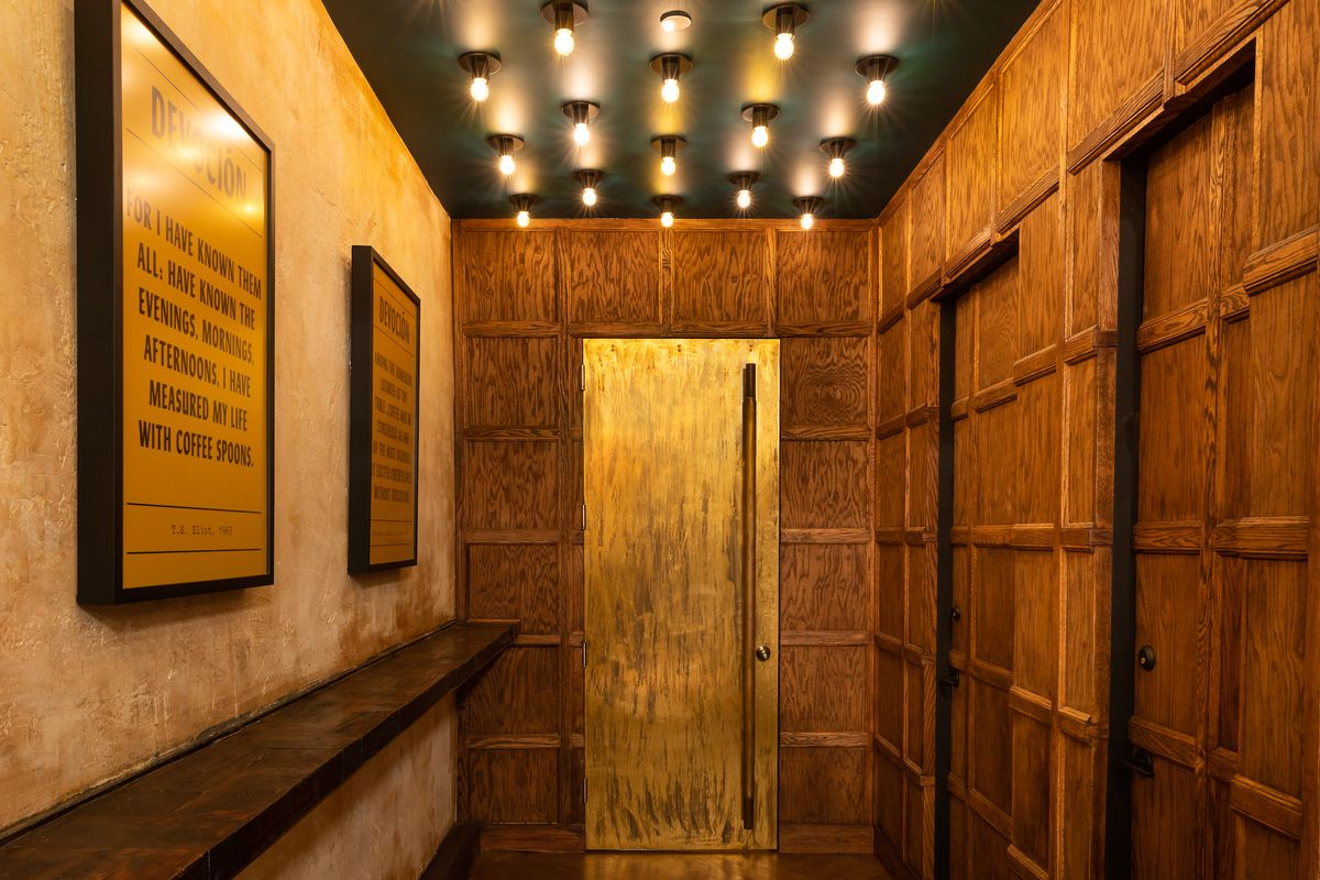 An image showing the interiors of a speakeasy bar with a brass door in the center, a green ceiling with exposed lightbulbs, and wood-paneled walls.