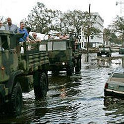 """President Bush, third from left, checks out the damage in New Orleans on Monday from the back of a truck. """"My impression of New Orleans is this: That there is a recovery on the way,"""" the president said."""