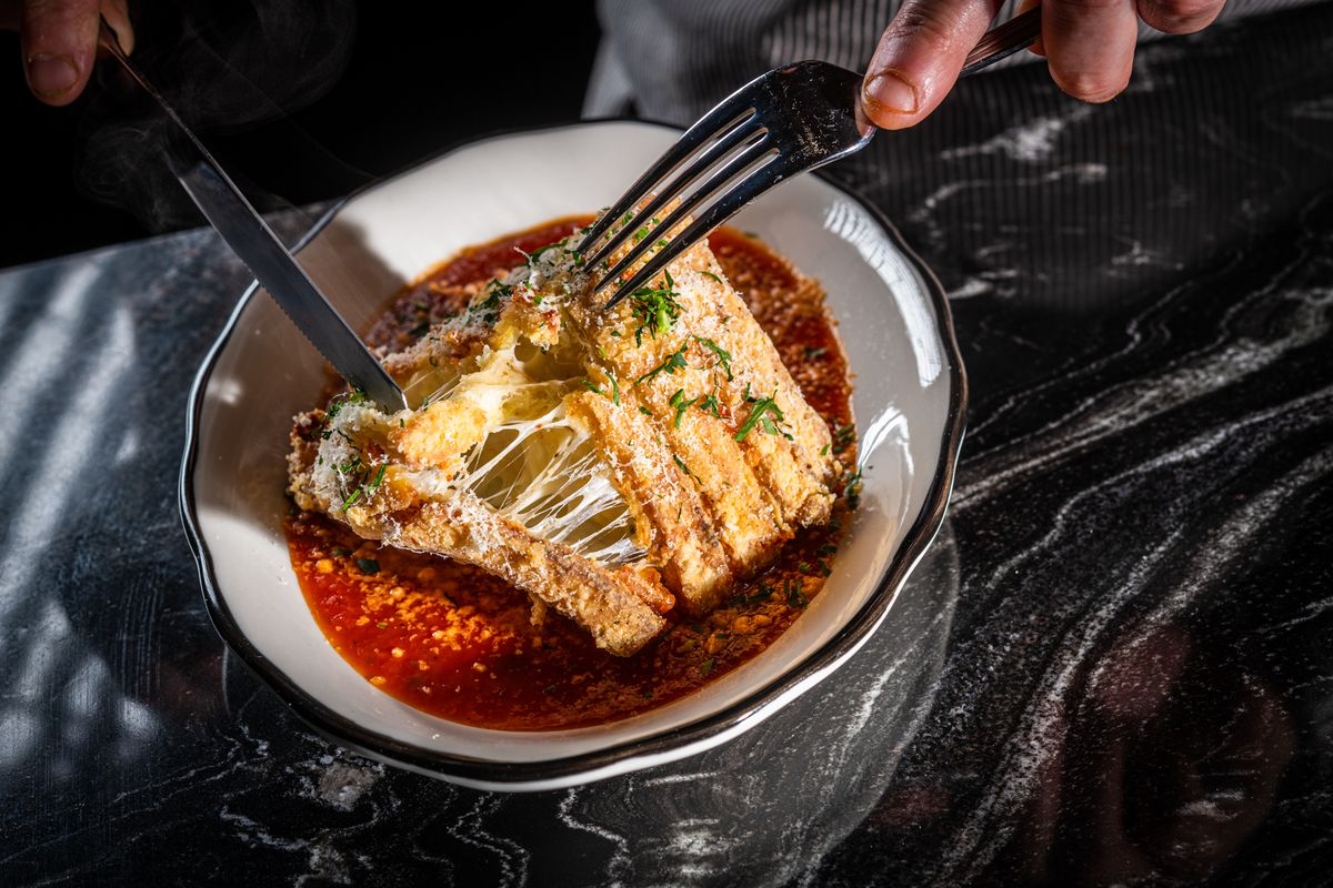 Mozzarella in carrozza layers low-moisture, stringy Grande cheese with sliced bread and a puree of roasted garlic, lemon, and herbs before it's all battered, fried, and served over tomato-basil sauce.