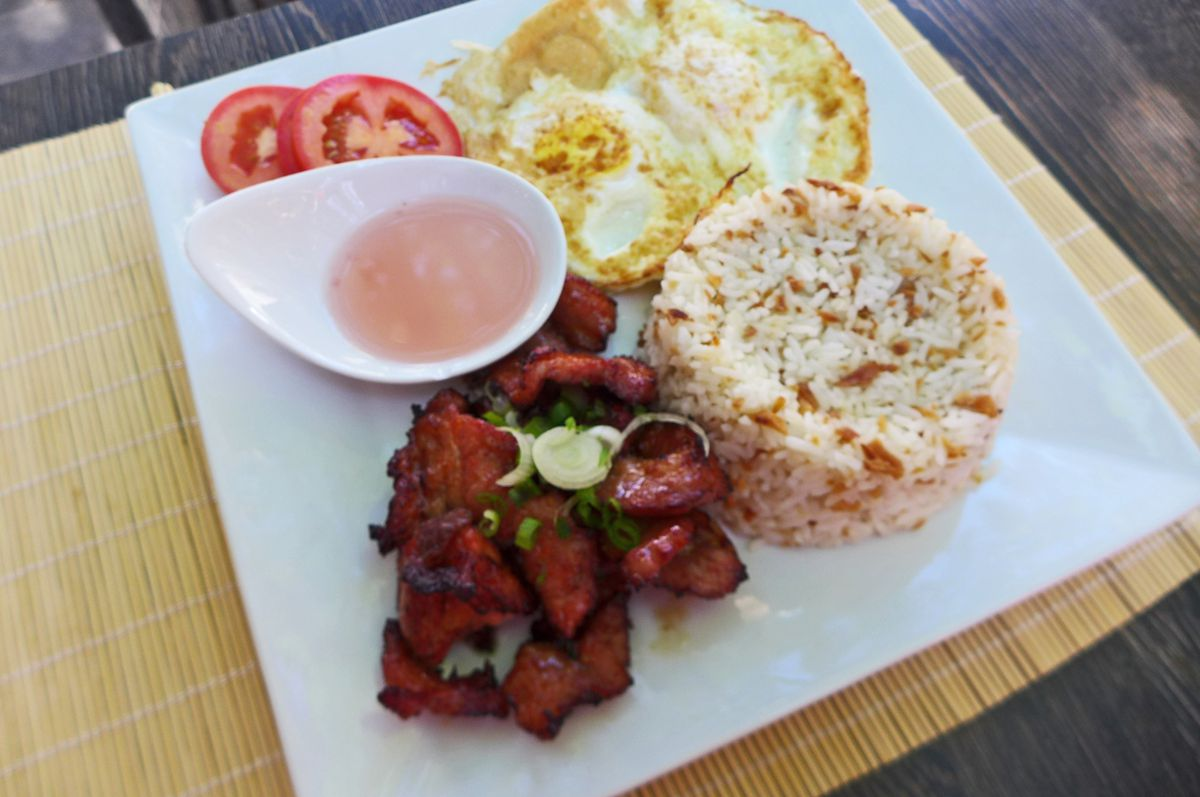 Heaps of rice, red pork tidbits, fried eggs, and sliced tomatoes, with a bowl of pink vinegar.