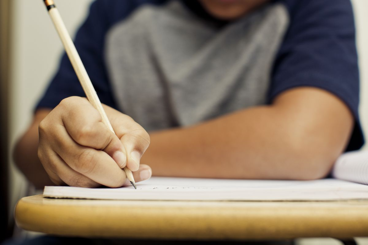 Student holds a pencil to a notebook placed on a desk.