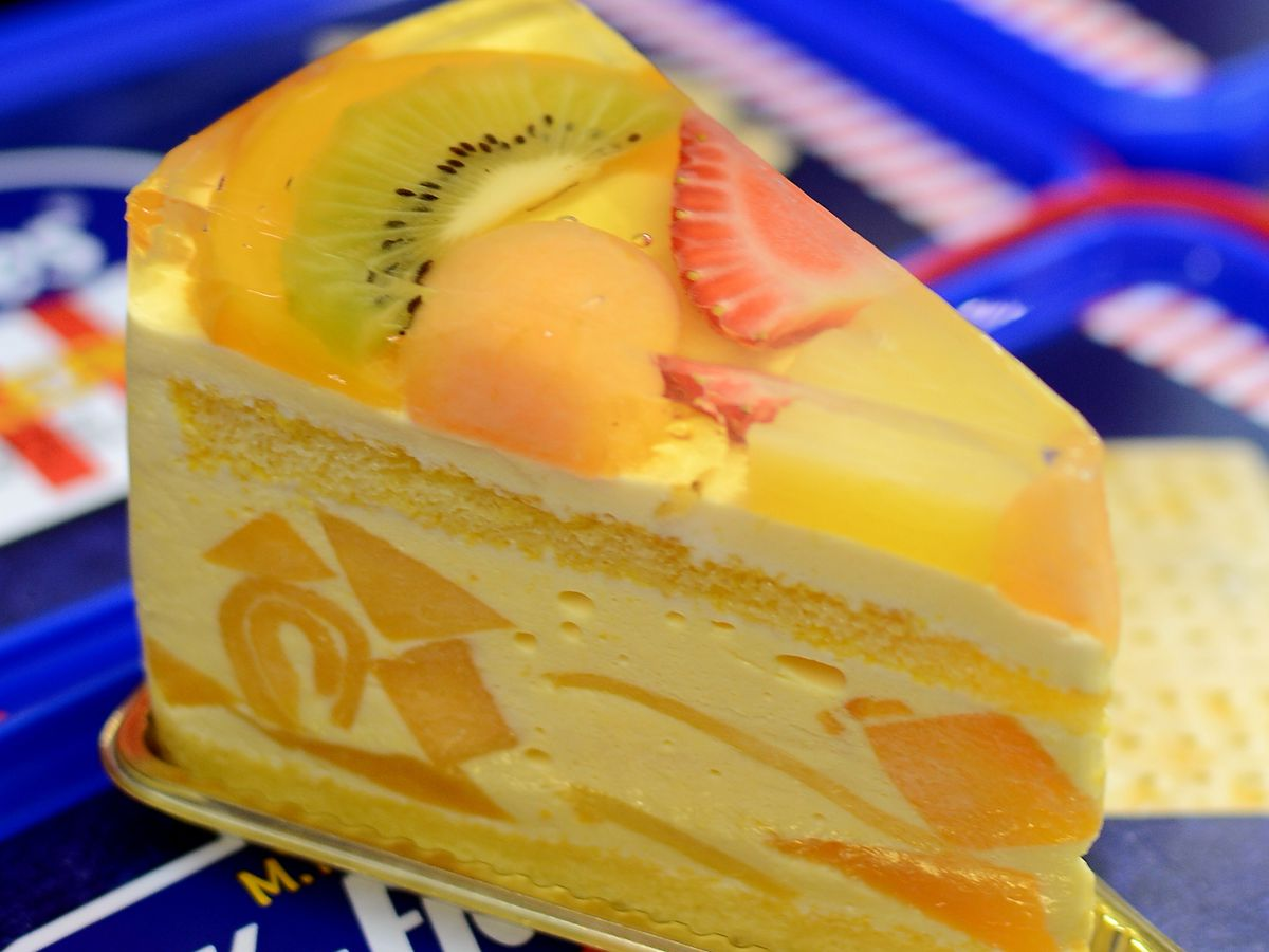 A slice of mango cake with fresh fruit on top.