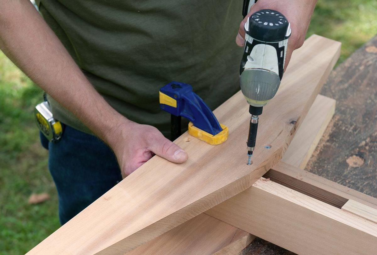 Man Attaches Feet And Brackets Of Picnic Table