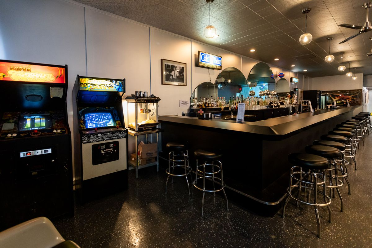 A bar with retro game consoles and a mirror shaped like a cloud.
