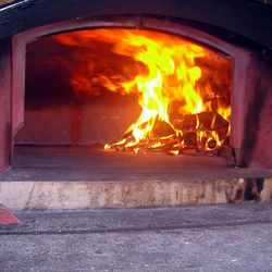 The fire crawls up to the roof of the oven.