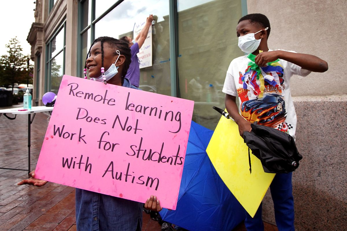 A girl holds a sign at a protest that reads: Remote learning does not work for students with autism.