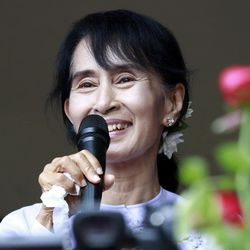 Myanmar pro-democracy leader Aung San Suu Kyi talks to supporters at the headquarters of her National League for Democracy party in Yangon, Myanmar Monday, April 2, 2012. Suu Kyi claimed victory Monday in Myanmar's historic by-election, saying she hoped it will mark the beginning of a new era for the long-repressed country.