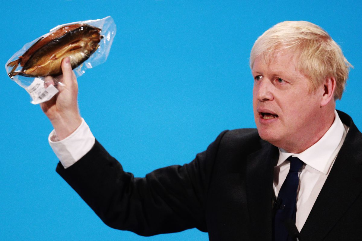 Boris Johnson waves a smoked kipper around on stage as part of Conservative Leadership Hustings against Jeremy Hunt, both men vying to be Prime Minister