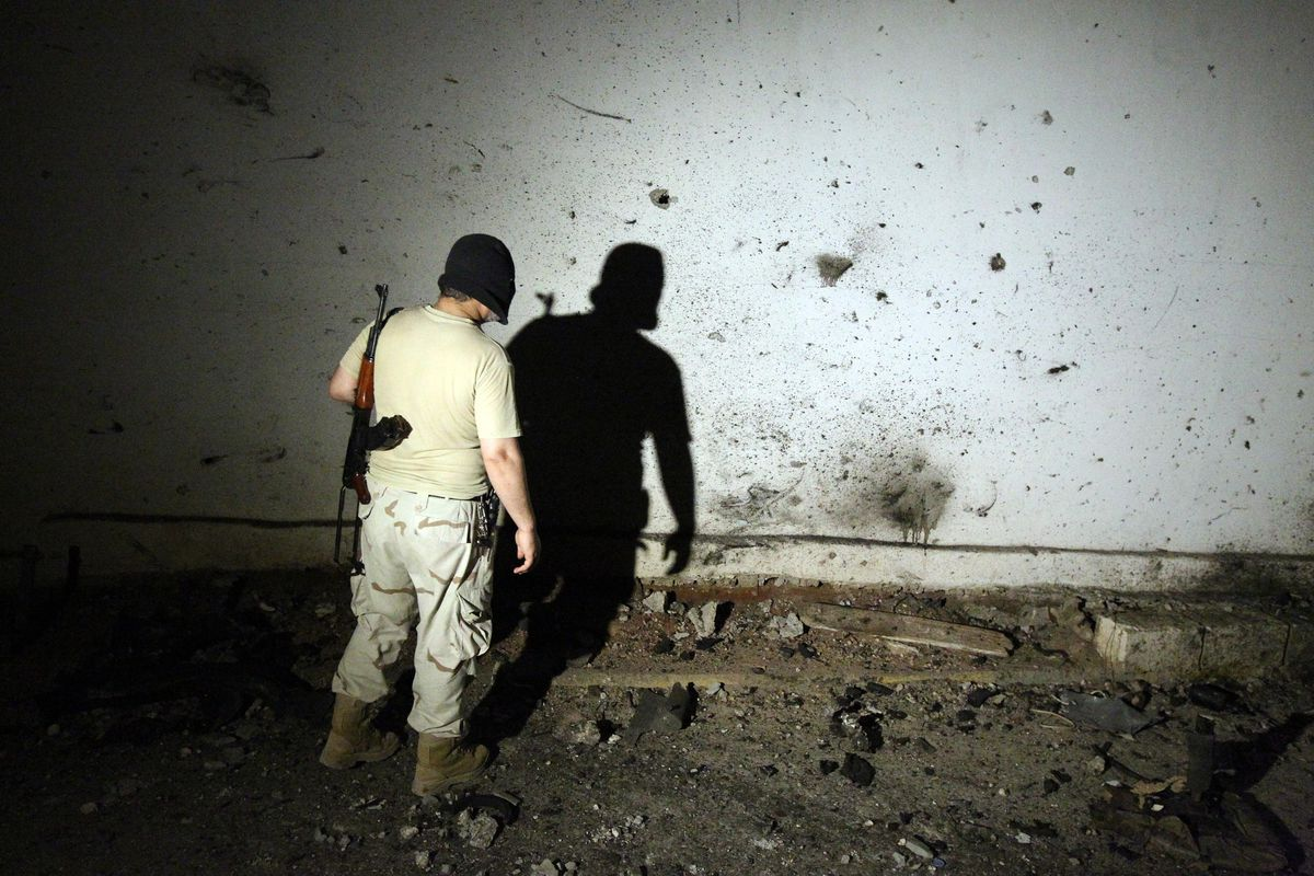 A Libyan fighters contemplates damage after a suicide bombing at a special forces installation in Benghazi.